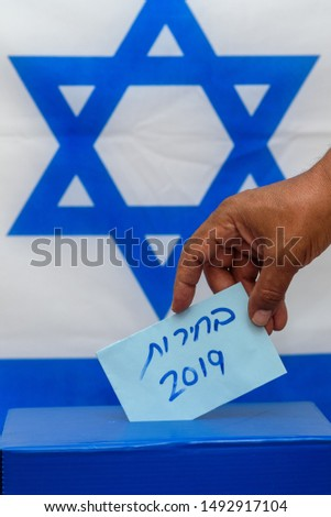 Election in Israel - voting at the ballot box. The hand of man putting vote in the ballot box. Israeli Flag on background. Hebrew text Elections 2019. #1492917104