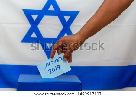 Election in Israel - voting at the ballot box. The hand of man putting vote in the ballot box. Israeli Flag on background. Hebrew text Elections 2019. #1492917107
