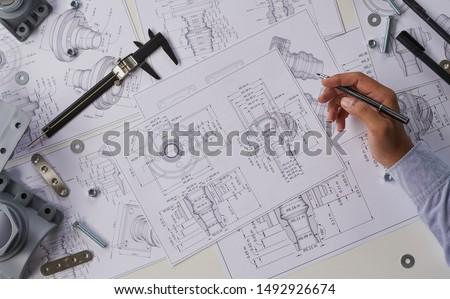 Engineer technician designing drawings mechanicalparts engineering Enginemanufacturing factory Industry Industrial work project blueprints measuring bearings caliper tools #1492926674