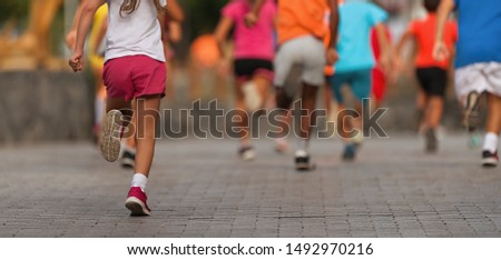 Running children, young athletes run in a kids run race,running on city road detail on legs #1492970216