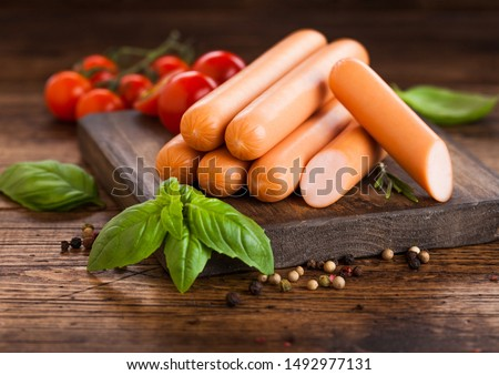 Classic boiled meat pork sausages on chopping board with pepper and basil and cherry tomatoes on wooden background. Snack for kids #1492977131