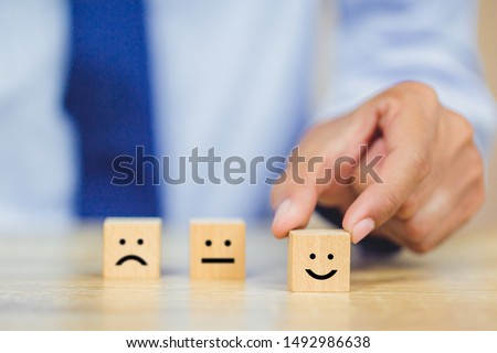 customer pressing smiley face emoticon on wood cube, Service rating, satisfaction concept. #1492986638