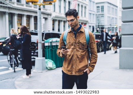 Frowning handsome Hispanic male in eyeglasses wearing brown suede jacket with backpack and earphones messaging on cellphone while waiting for green traffic light on crosswalk with hand in pocket  #1493022983