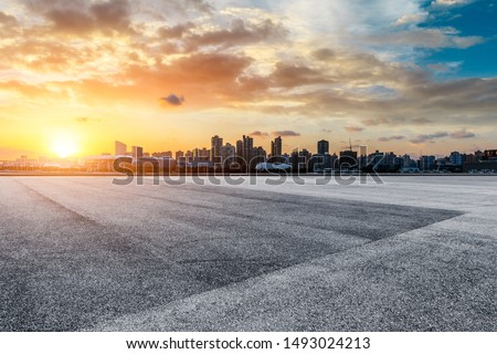 Asphalt race track and city skyline at sunset in Shanghai,China.