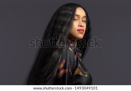 gorgeous mixed race model in studido shoot with long wavy wig on Dark background Royalty-Free Stock Photo #1493049101