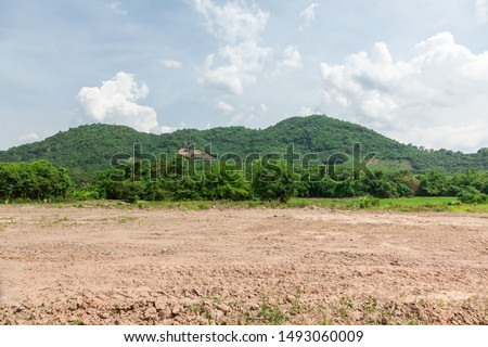 Empty dry cracked swamp reclamation soil, land plot for housing construction project with car tire print in rural area and beautiful blue sky with fresh air Land for sales landscape concept. Royalty-Free Stock Photo #1493060009