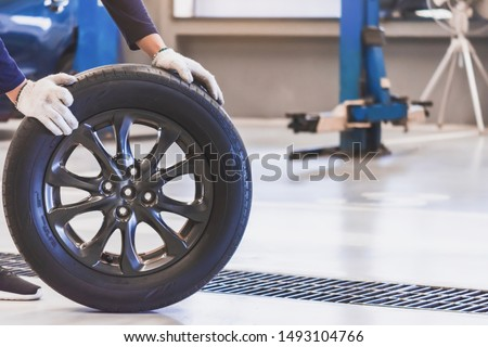 Asian man mechanic inspection service maintenance car holding tyre or tire car inspection for Measure quantity Inflated Rubber tires car.Close up hand push wheel to for tyre pressure automotive #1493104766