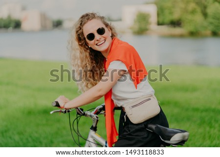 Outdoor shot of pleased active European woman with curly bushy hair, spends weekend riding bicycle, wears sunglasses, poses in park against green grass, being in good mood. Female bicyclist. #1493118833
