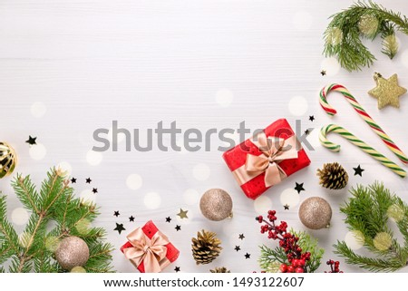 Christmas border flat lay with pine, presents, golden elements, candy canes, confetti. Christmas template on light wood #1493122607
