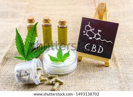 Full spectrum CBD and THC cannabis oils, pills and cbd lotion on hemp cloth with chemical structure on blackboard Royalty-Free Stock Photo #1493138702