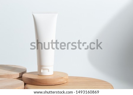 cosmetic fashion cream lotion liquid bottle tube product packaging and long shadow on white background wood plate dish in beauty skincare spa treatment healthcare medical concept Royalty-Free Stock Photo #1493160869