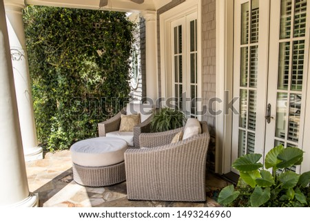outdoor patio porch of traditional upgraded custom home with seating for entertaining and dining with a greenery wall #1493246960