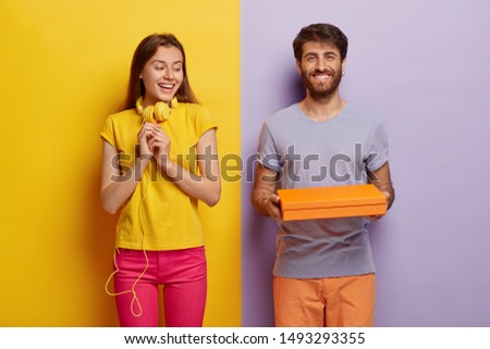 Pleasant looking woman keeps hands in anticipation, looks curiously at cardboard box, being interesting what is inside. Happy young man holds little contrainer or package, gives present to girlfriend #1493293355