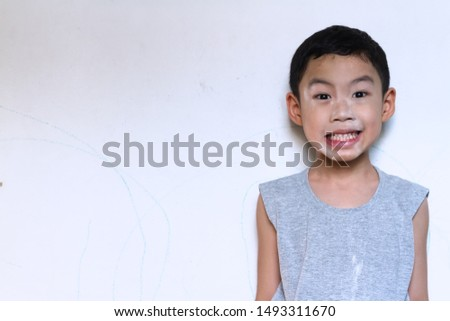 Asian black hair naughty boy age 5 years old wear gray t-shirt use baby powder on his face and say cheese for smiling with white cement wall background. Happy acting picture concept.