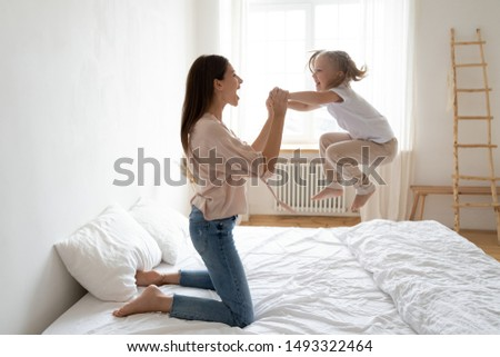 Little preschool daughter frolics jumping on bed holding cheerful mothers hands, after daytime or night sleep girl and her mom spend active carefree time do exercise or just fool around in the bedroom #1493322464