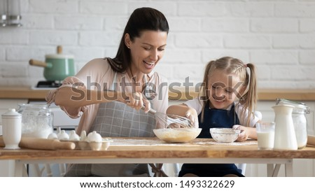 Pretty woman and little adorable daughter sitting at table in kitchen cook together stirring eggs for pie, cookies or pancakes, teach kid recipes, embodiment of ideal wife of mom and housewife concept Royalty-Free Stock Photo #1493322629