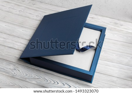 blue stylish square cardboard box for a photo album. Bright original box for white wedding album. leather family photo book in the open box blue cardboard box for a photo book