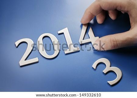 Man changing metallic numbers to year 2014. #149332610