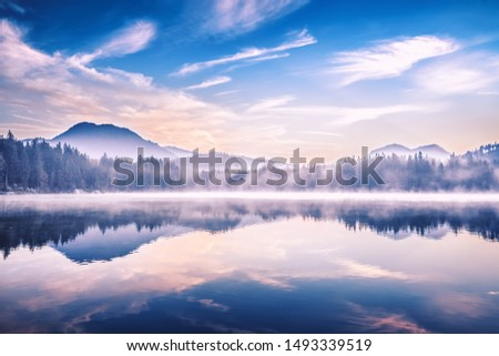 Hintersee lake in Germany, located in Ramsau parkland. Beautiful morning scenery of Alpine lake, misty picturesque landscape. Charming Alps in Background. European popular recreation site.