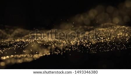 Gold glitter light particles splash wave, bokeh effect on black background. Shining gold sparks, shimmering sparkles glow in wave motion