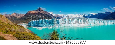 Panoramic view of the gigantic Perito Moreno glacier, its tongue and lagoon in Patagonia in golden Autumn, Argentina, sunny day, blue sky #1493355977