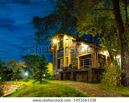 Large wooden house. A stone path in the cottage. A path leads to a wooden house. Lighted two-story cottage at night. Private house in the forest. Holiday cottage in the country. Summer vacation #1493361338