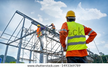 Engineer technician watching team of workers on high steel platform,Engineer technician Looking Up and Analyzing an Unfinished Construction Project. #1493369789