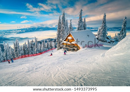 The best popular winter ski resort with skiers in Romania. Amazing touristic and winter holiday destination. Winter sunny day in Poiana Brasov ski resort, Transylvania, Romania, Europe Royalty-Free Stock Photo #1493373995