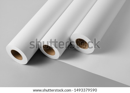 Blank white paper rolls isolated on gray background. Mockup paper for magazines, catalogs or newspapers isolated on gray backdrop, Printing house theme or wrapping paper for presents Royalty-Free Stock Photo #1493379590