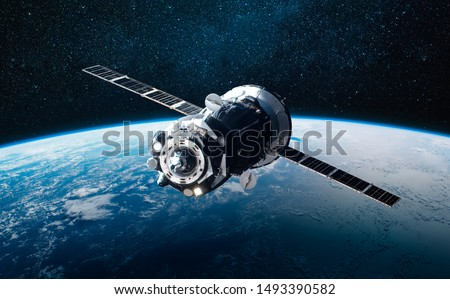 Cargo space craft and Earth planet. Dark background. Sci-fi wallpaper. Elements of this image furnished by NASA #1493390582