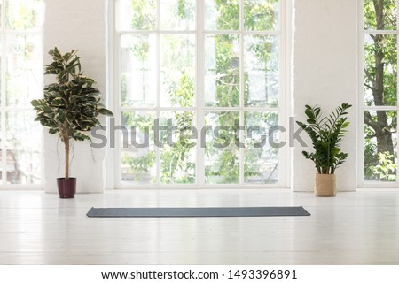 Empty fitness center interior with big windows and unrolled yoga mat on wooden floor, modern loft studio, comfortable space for work out and sport training, exercise, plants in pots #1493396891