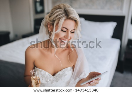 A beautiful, smiling blonde bride in a white dress is sitting on the bed and looking at the phone, reading a message and drinking champagne. Wedding portrait of a cheerful girl. Royalty-Free Stock Photo #1493413340