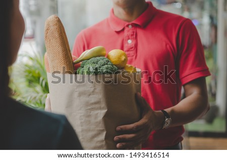 smart food delivery service man in red uniform handing fresh food to recipient and young woman customer receiving order from courier at home, express delivery, food delivery, online shopping concept  #1493416514