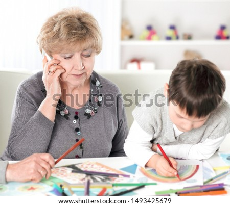 modern grandparents visiting grandson sitting at the table in the nursery. concept of education #1493425679