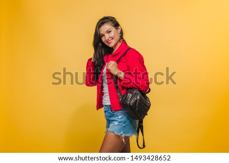 Girl on yellow background in red jacket with backpack #1493428652