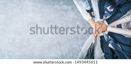 Close up top view of young business people putting their hands together. Stack of hands. Unity and teamwork concept. #1493445611