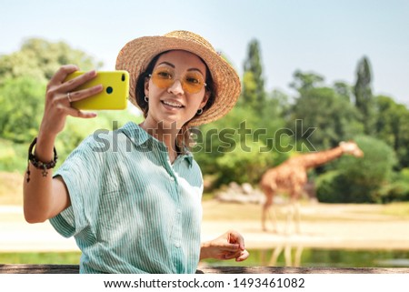 Happy asian zoology student girl taking selfie photo on smartphone while giraffe drinking from lake #1493461082