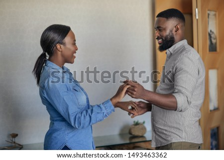 Smiling young African American couple playfully dancing hand in hand together in their living room at home #1493463362