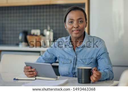 Portrait of a smiling young African American woman sitting at her kitchen table at home going over her finances and using a digital tablet #1493463368