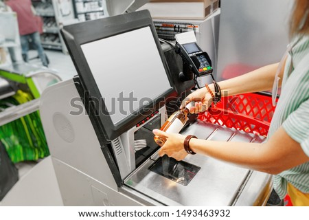 Girl customer scans bottle of wine at the self-service checkout in the grocery supermarket shop Royalty-Free Stock Photo #1493463932