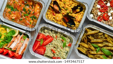 Food delivery.Different aluminium lunch box with healthy natural food pasta pesto, spelt, paella, quinoa, chicken salad, curry.  airlines food. airline meals and snacks . takeaway  #1493467517