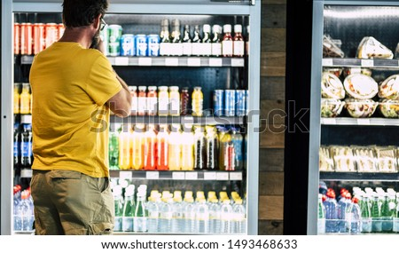 man alone and isolated at the supermarket or minimarket choosing his drink or snack in big fridge with lots of products - difficult select and choose #1493468633