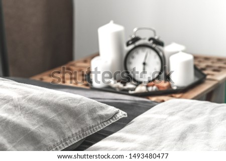 Cozy gray bedroom interior with comfortable bed near the wooden night table with candle, alarm clock and dried flowers. Cozy atmosphere at home. Warming up the cold evenings. Vintage furniture.  #1493480477