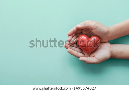 hands holding red heart on blue background, health care, hope, love, organ donation, wellbeing, family insurance and CSR concept, world heart day, world health day, National Organ Donor Day #1493574827
