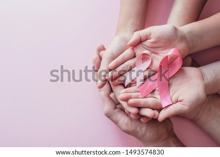 hands holding pink ribbons on pink background, Breast cancer awareness and October Pink day, world cancer day, national cancer survivor day Royalty-Free Stock Photo #1493574830