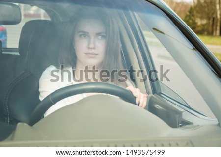 The girl thoughtfully drives the car, drives the car. Woman driving. #1493575499
