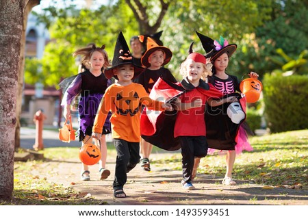 Child in Halloween costume. Mixed race Asian and Caucasian kids and parents trick or treat on street. Little boy and girl with pumpkin lantern and candy bucket. Baby in witch hat. Autumn holiday fun. #1493593451