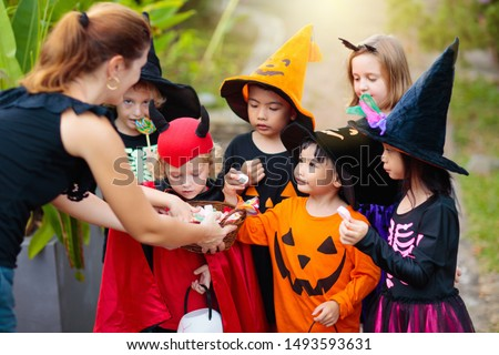 Kids trick or treat on Halloween night. Mixed race Asian and Caucasian children at decorated house door. Boy and girl in witch and vampire costume and hat with candy bucket and pumpkin lantern.  #1493593631