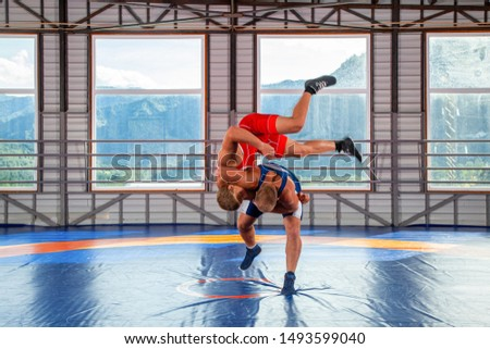 The concept of fair wrestling. Two greco-roman  wrestlers in sportwears wrestles and  makes a throw  on a wrestling carpet in the gym.The concept of male wrestling and resistance