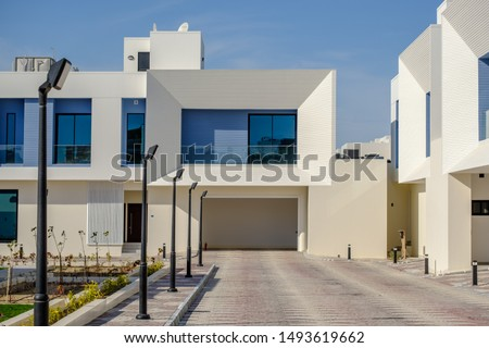 White and blue modern villas in a Middle Eastern, high-end, luxury housing development on a sunny day with strong shadows. #1493619662